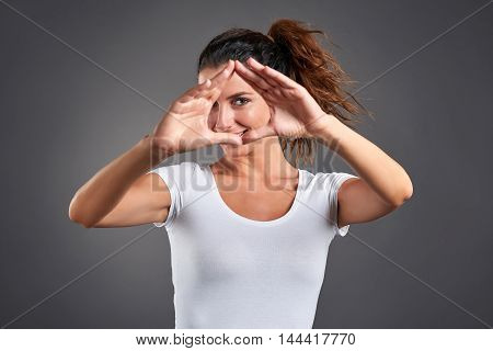 A beautiful young woman shaping a triangle with her hands and looking through of it.