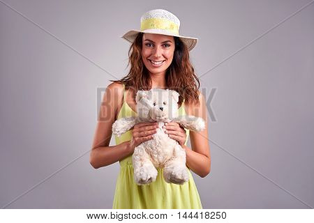 A beautiful young woman smiling and holding a teddybear in a green dress and a hat