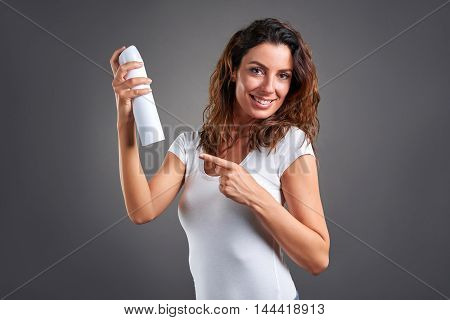A beautiful young woman smiling while using a hairspray