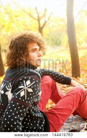 Upset young man resting in autumn park, backlight