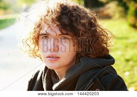 Portrait of a young depressed man in autumn park, looking at camera