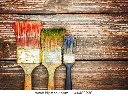 a set of paintbrushes with paint on them in a row on a stained wooden background toned with a retro vintage instagram filter app or action effect