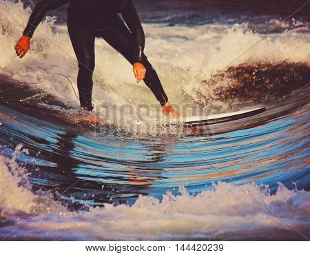 a surfer riding a wave in a full wet suit toned with a retro vintage instagram filter app or action effect