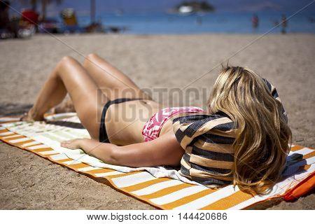 Blurred blonde girl on the beach sunbathing