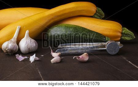 Garlic and galic crusher and three zuccini two yellow and green.Wooden background.Horizontal shot .Free space