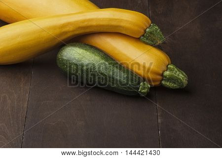 Two yellow big and medium and small green zucchini on wooden table.Family of zuccini.Free space