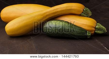 Two yellow big and medium and small green zucchini on wooden table.Family of zuccini.