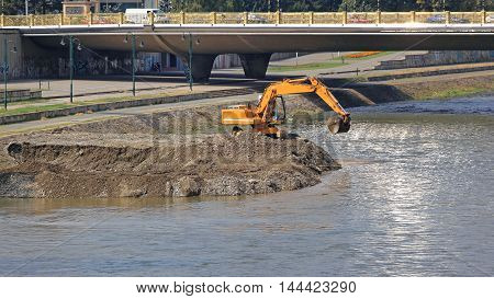 Excavator Machine Digging Levee at River Embankment