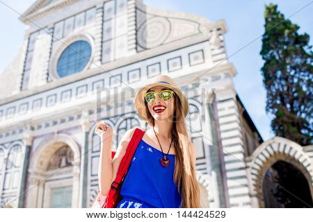Young female traveler in blue dress with backpack standing in front of Santa Maria Novella church in Florence.