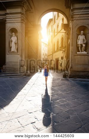 Beautiful arch near Uffizi museum with woman walking in the morning in Florence. Vacation in Italy