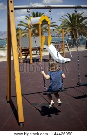 A Lonely Young Girl Playing On Swing In Playground