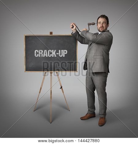 Crack Up-pp text on blackboard with businessman drilling his head