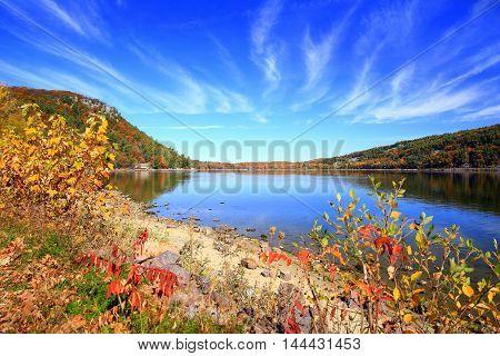 Autumn foliage along calm lake shoreline, hiking trails at Devil's Lake State Park,  Wisconsin