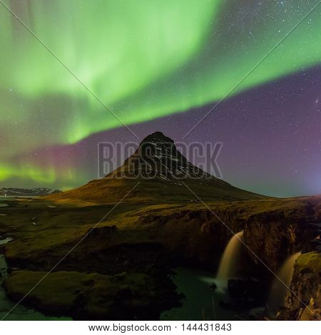 Green Northern lights over Kirkjufell volcano night view, natural landscape background