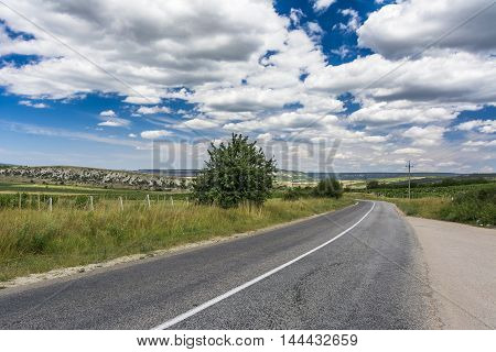 Empty road through a mountain valley. Beautiful cloudy sky. Stock photo.