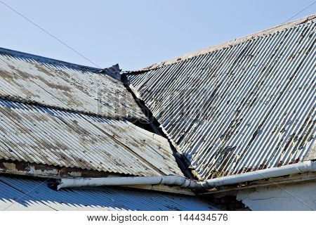 many broken corrugated iron roof sheets on an old abandoned house