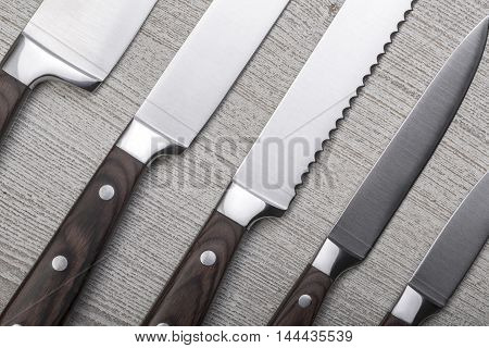 set of high quality kitchen knives on wooden table