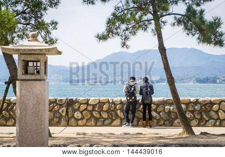 Hiroshima, Japan - March 16, 2016: Miyajima on March 16, 2016. A Couple of Tourist are standing at Miyajima beach.
