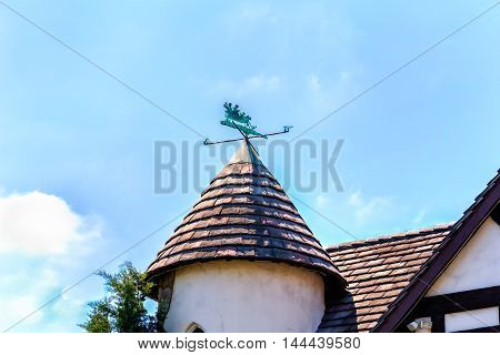 conical slat roof with charming patinated brass vane and blue sky with clouds
