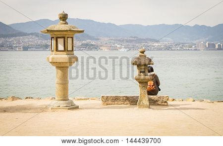 Hiroshima, Japan - March 16, 2016: A Couple of Tourist are standing at Miyajima beach.