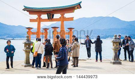Hiroshima, Japan - March 16, 2016: Miyajima on March 16, 2016. Chinese tourists are taking photo of Miyajima Torii.