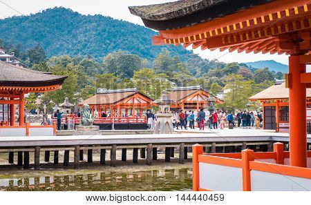 Hiroshima, Japan - March 16, 2016: Tourists are taking picture of Miyajima Torii from the corridor of the floating temple.