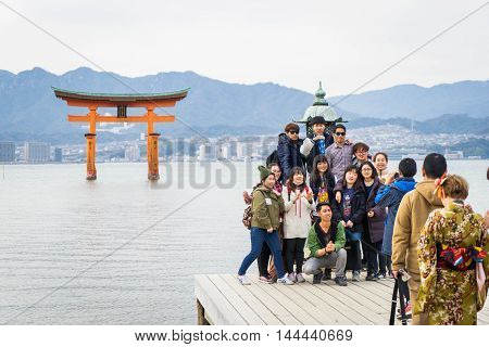 Hiroshima, Japan - March 16, 2016: Miyajima on March 16, 2016. A large group of tourists is taking picture with the Famous floating tore.