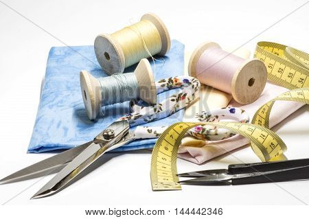Measuring tape, scissors and threads on white