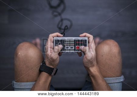 Gothenburg, Sweden - January 31, 2015: A young man's hands using a Nintendo game controller, a remote controller for the Nintendo Entertainment System developed by Nintendo Co., Ltd. in the 1980s.