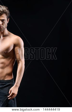 Sexy young man is posing with half naked muscular torso. He is standing and looking at camera with passion. Isolated on black background. Copy space in right side