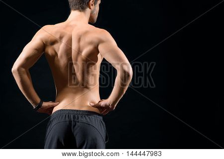 Confident young man is standing with arms akimbo. He is showing his trained muscular back. Isolated and copy space in right side