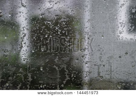 With a rain soaked screen a view of a neighboring house.