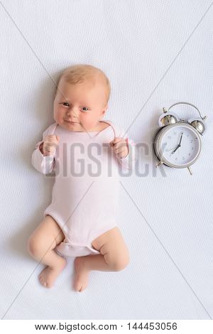 Come have some fun with me. Top view of little baby girl lying on diaper and looking into camera next to alarm isolated on white