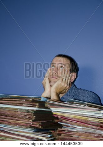 Man hiding behind piles files looking up at the ceiling. Example of an overworked, overwhelmed employee.