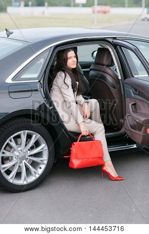 One Successful business woman. Young lady sitting on a backseat of a luxury car