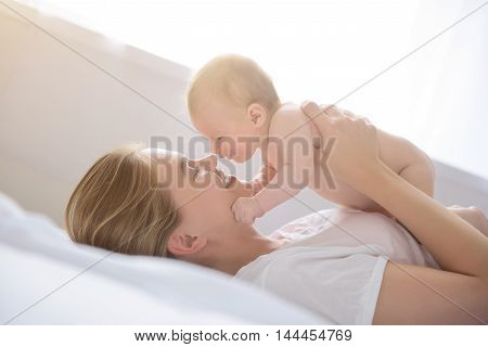 Mama hugs are the most favorite. Shot of baby girl in arms of her happy smiling mother lying in bed and playing