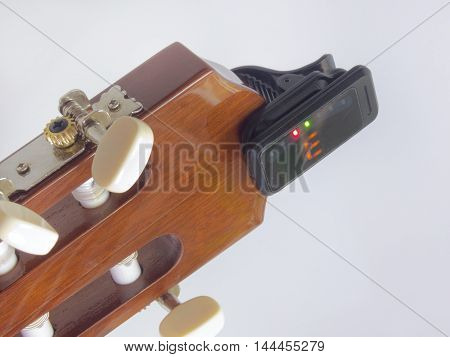 The headstock of the guitar with installed clip-on tuner that shows the note e