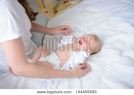 Time for diaper change. Cropped shot of small child lying and crying while his mother undressing him in bed