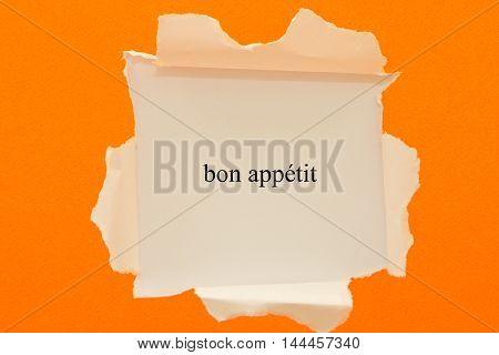 french word bon appetit written under torn paper.