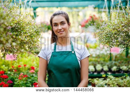 Young beautiful female florist posing, smiling among flowers.