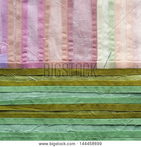 Close up photo of downside of quilt in pink and green colors