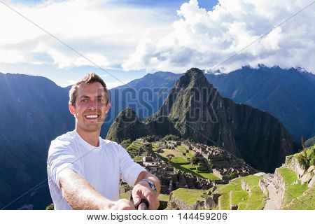 Young man taking a selfie with Machu Pichu in the background. May 16 2016 Machu Pichu Peru.