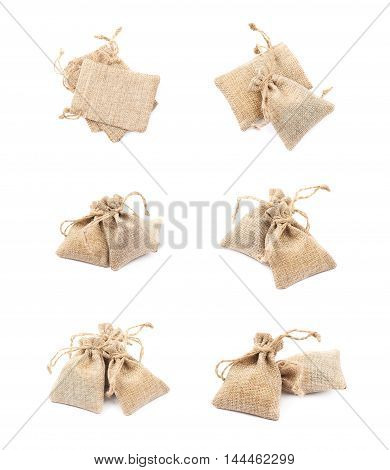 Pile of multiple tiny sackcloth bags with a tie string, composition isolated over the white background, set of six different foreshortenings