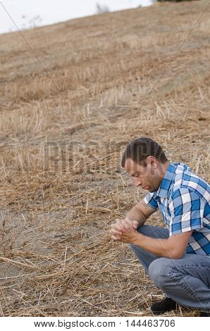 Man crouching down and praying with his hands clasped outside on a hill side wearing a plaid shirt.