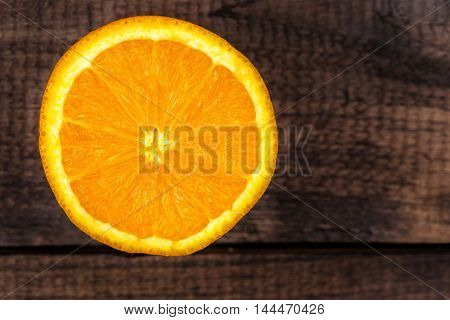 A isolated half orange on wooden background