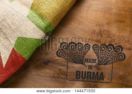 Flag of the state of Burma on a wooden background and stamp made in Burma.