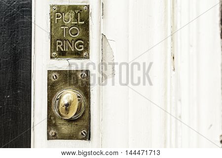 An Old Fashion golden ring bell on a white door