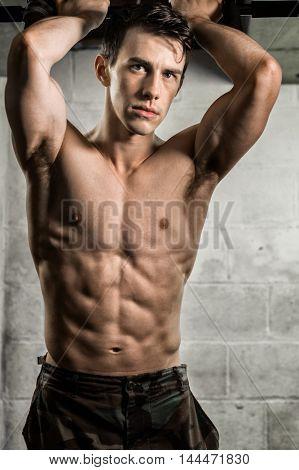 Athletic man posing with flexed muscles in doorway.