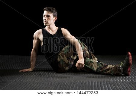 Athletic man stretching. Studio shot over black.