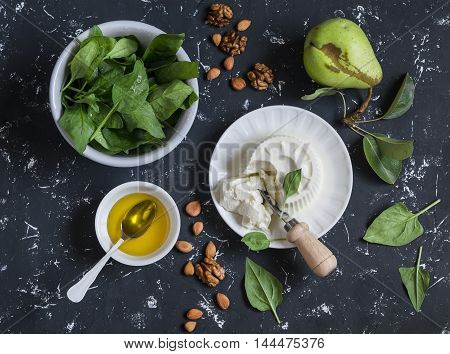 Ingredients for salad - fresh spinach soft goat's cheese pear honey nuts. On a dark background top view
